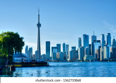 Toronto, Canada - July 8, 2018: Cityscape of Toronto, Ontario, Canada, dominated by the CN Tower landmark, seen from the island Lake Ontario. Business buildings, skyscrapers panorama silhouette