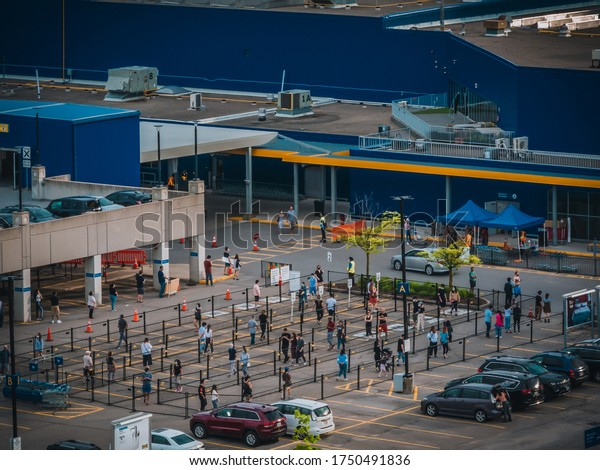 TORONTO, CANADA - JUNE 05, 2020: Line of socially distancing shoppers divided  by a fence at IKEA North York parking lot from above