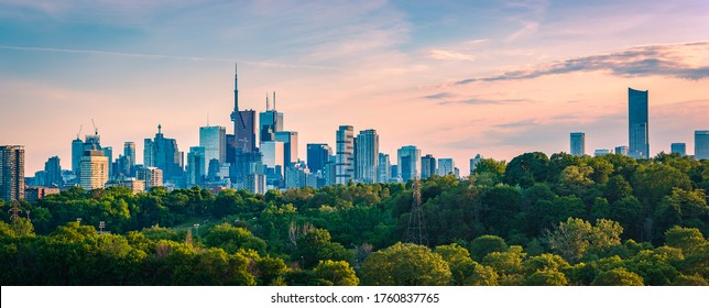 TORONTO, CANADA - JUNE 20 , 2020:  Panoramic Toronto Skyline from Riverdale Park - facades and rooftops of skyscrapers in  Financial District  at sunset