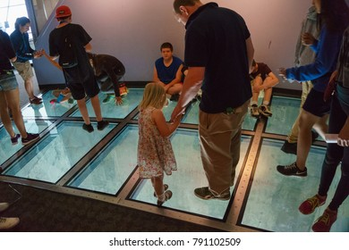 TORONTO, CANADA - JUNE, 2016: Man walking on the glass floor of the CN tower, 350 meters above ground level. Visitors are allowed to walk or crawl across the glass floor or sit or even jump on it.