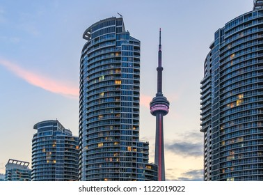 TORONTO, CANADA - JUNE 24 2018 :  The CN Tower  among skyscrapers illuminated at sunset