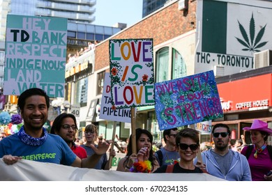 TORONTO, CANADA - JUNE 25, 2017: Marchers holding signs at 2017 Toronto Pride Parade.