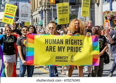 TORONTO, CANADA - JUNE 25, 2017: Amnesty International marches with HUMAN RIGHTS ARE MY PRIDE banner at 2017 Toronto Pride Parade.