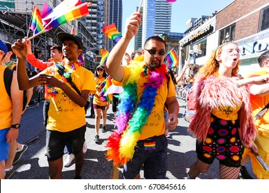 TORONTO, CANADA - JUNE 25, 2017: UNIVERSITY OF WATERLOO marches in orange shirts holding rainbow flags at 2017 Toronto Pride Parade.
