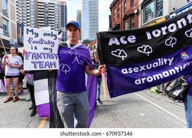 TORONTO, CANADA - JUNE 25, 2017: ASEXUALS march, holding MY ONLY FANTASY IS MY FANTASY TEAM sign and banner, at 2017 Toronto Pride Parade.