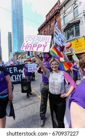 TORONTO, CANADA - JUNE 25, 2017: ASEXUALS march, holding ASEXUAL AND HAPPY sign at 2017 Toronto Pride Parade.