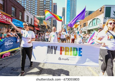 TORONTO, CANADA - JUNE 25, 2017: SHOPIFY employees march with banner at 2017 Toronto Pride Parade.