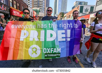 TORONTO, CANADA - JUNE 25, 2017: OXFAM marches with rainbow banner at 2017 Toronto Pride Parade.