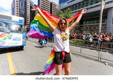 TORONTO, CANADA - JUNE 25, 2017: WALLMART employees march holding rainbow flag at 2017 Toronto Pride Parade.