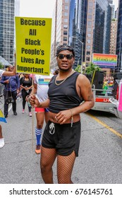 TORONTO, CANADA - JUNE 25, 2017: Marcher holding BECAUSE ALL BLACK PEOPLE'S LIVES ARE IMPORTANT sign at 2017 Toronto Pride Parade.