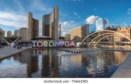 TORONTO, CANADA - JUNE 28, 2017: Toronto City Hall and Nathan Phillips Square at sunset on June 28, 2017 in Toronto, Canada. people walk by Toronto sign at sunset.