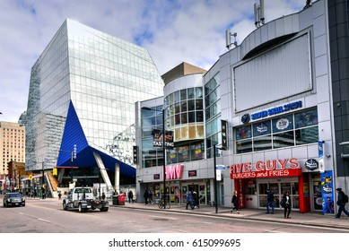 TORONTO, CANADA - MAR 29, 2017:  Section of Yonge Street near Dundas that includes a Five Guys, HMV with closing signs in window, and glass building of Ryerson University.