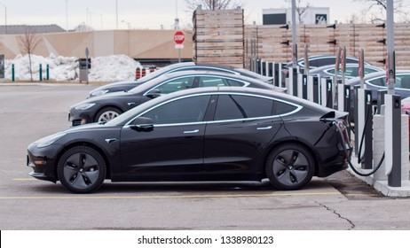 TORONTO, CANADA - MARCH 13, 2019: Tesla Model 3 parked plugged-in at a Tesla Supercharger with other vehicles in Toronto, Ontario, Canada on March 13th, 2019.
