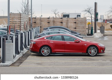 TORONTO, CANADA - MARCH 13, 2019: Tesla Model S parked plugged-in at a Tesla Supercharger with other vehicles in Toronto, Ontario, Canada on March 13th, 2019.