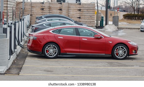 TORONTO, CANADA - MARCH 13, 2019: Tesla Model S parked charging at a Tesla Urban Supercharger with other vehicles in Toronto, Ontario, Canada on March 13th, 2019.