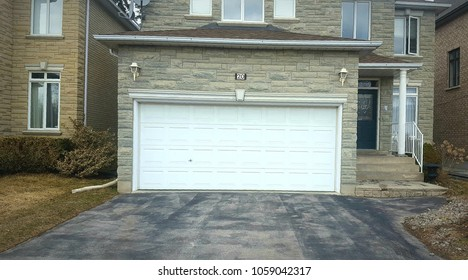 TORONTO, CANADA - MARCH 22, 2018: Garage doors and driveway outside a residential building.