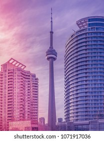 TORONTO, CANADA - MARCH 26, 2018:  The CN Tower between the two nearby skyscrapers at sunset