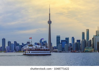 TORONTO, CANADA - MAY 12 , 2016 :Toronto skyline at sunset; a ferry departs from Toronto Islands to the mainland .