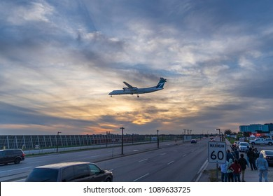 TORONTO, CANADA - MAY 12, 2018: C-GWEP WestJet Encore De Havilland Canada DHC-8-400 is landing over Airport Road at Toronto Lester B. Pearson Airport at sunset while people watching the landing