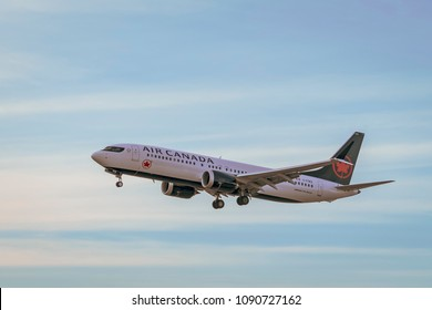 TORONTO, CANADA - MAY 12, 2018:  Air Canada Boeing 737 is landing at Toronto Lester B. Pearson Airport at sunset - isolated on a blue cloudy sky background