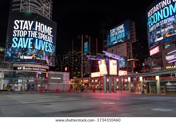 "TORONTO, CANADA - May 12, 2020: Toronto's Young-Dundas Square empty at empty, with digital billboards reading ""Stay home. Stop the spread. Save lives."" during the COVID-19 pandemic."