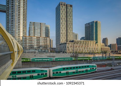 TORONTO, CANADA - MAY 14, 2018:  High - rise buildings at Concord Cityplace. GO trains  passing by the complex at sunset