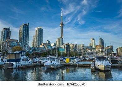 TORONTO, CANADA - MAY 18, 2018: The Marina of Toronto .The CN Tower, new high - rise buildings, skyscrapers boats at sunset with a blue sky