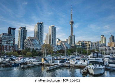 TORONTO, CANADA - MAY 18, 2018:  The CN Tower, new high - rise buildings, skyscrapers, the Marina and yachts at sunset with a blue sky