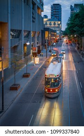 TORONTO, CANADA - MAY 26, 2018: An old red Bombardier streetcar on Queen Street West, near Sheraton Centre, at night with headlights on - from above