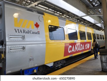 Toronto, Canada - May 27, 2017: Passenger walks fast in front of Canada 150 painted in one of the cars of Via Rail.