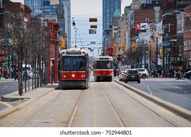 TORONTO, CANADA - MAY 7, 2014: #510 Spadina streetcar line runs through Toronto's Chinatown at Dundas Street.  Several Chinese signs translate to souvenir shops, arts and crafts, and restaurants