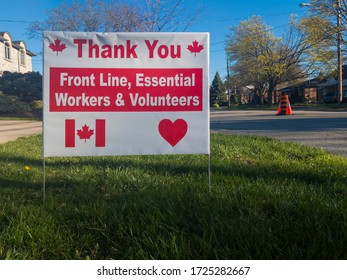 Toronto, Canada - May 7, 2020: Thank you front line, essential workers and volunteers sign with anadian flag and maple leafs during corona virus outbreak. Selective focus.