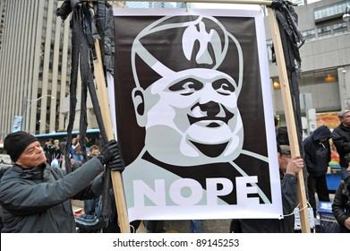 TORONTO, CANADA – NOV 19:  Unidentified protesters hold a Benito Mussolini style sign protesting Mayor Ford's proposed cuts and his attempt to evict them from Saint James Park Nov 19, 2011 in Toronto.