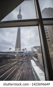 TORONTO, CANADA - NOVEMBER 13, 2018: Go Transit train leaving Union station passing in front of CN Tower. Go Transit is the commuter transit system of Toronto & Ontario
