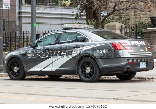 TORONTO, CANADA - November 16, 2019: Grey Toronto Police car parked on the side of a city street during the day.