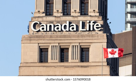 TORONTO, CANADA - November 24, 2019: Canada Life sign atop of their head office in Toronto with a Canadian flag seen waving in-front.