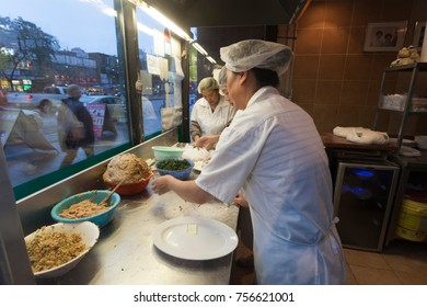 Toronto, Canada - Oct 14, 2017: Women preparing traditional dumplings at the front window of a chinese restaurant. China town in Toronto, Canada