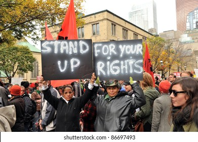 TORONTO, CANADA – OCT 15:  Unidentified demonstrators march to Saint James Park for the Toronto version of Occupy Wall Street, Oct. 15 2011.  The bank buildings on Bay Street are in background.
