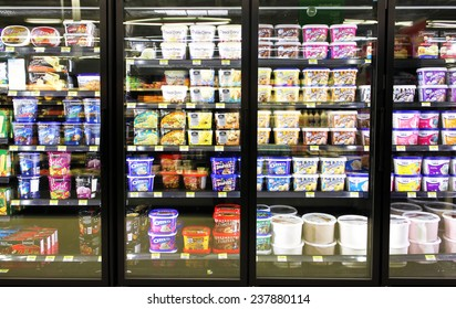 TORONTO, CANADA - OCTOBER 31, 2014: Different brands and flavors of ice cream on fridge shelves in a supermarket. Based on studies, half of the population in North America eat ice cream regularly.