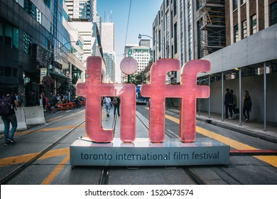 Toronto / Canada - Sep 5, 2019: A large TIFF sign on King Street in Toronto during the 2019 Toronto International Film Festival, with pedestrians walking through.