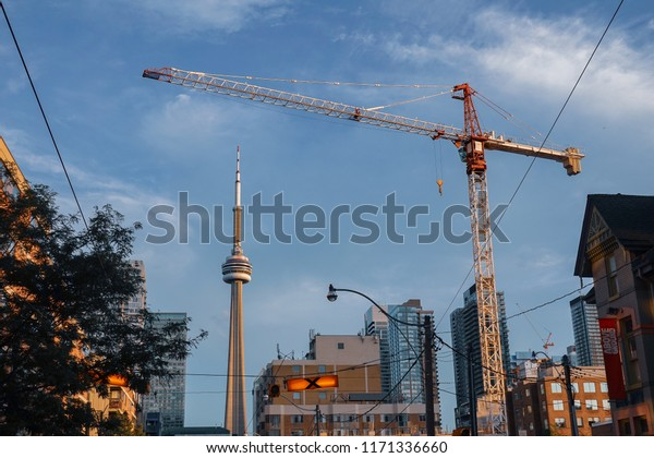 TORONTO, CANADA - SEPTEMBER 03, 2018: Urban landscape in Downtown Toronto; a crane and the CN Tower top on a blue cloudy sky background