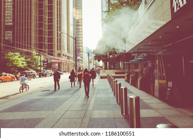 TORONTO, CANADA - SEPTEMBER 17, 2018: Rush hour at Toronto downtown, many people on the street. Sunset time with sun flares.
