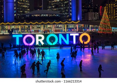 Toronto, Canada-December 12, 2017: People skating in Nathan Phillips Square at night.  The famous place is a major tourist attraction and recreational spot in the capital of the province of Ontario