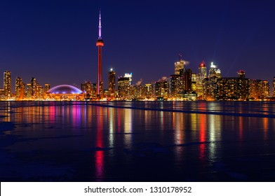 Toronto city skyline lights at night reflected on the frozen ice covered Lake Ontario
