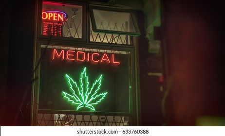 TORONTO - FEB 20, 2016: Medical marijuana retail storefront with neon sign pot leaf and open sign.