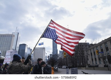 TORONTO - FEBRUARY 4:  Protesters waiving an American flag during a protest in front of the US Consulate to denounce Donald Trump's immigration policies on February  4, 2017 in Toronto, Canada.