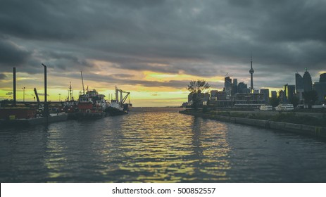 Toronto Golden Dusk Sunset Docks Port Tugs. Late afternoon, early evening sunset shot of downtown Toronto from them eastern ports area with docked tugboats. Edited in vintage film style.