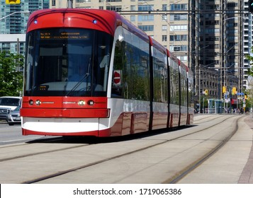 Toronto Harbourfront streetscape and urban scene. concrete and glass condominium buildings background. red streetcar. low angle perspective. bright summer day, steel tracks and light car traffic.
