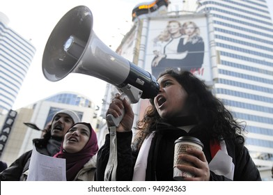 TORONTO - JANUARY 21: Egyptian teens  participating in a rally at Yonge and Dundas square   during the global day of support for the Egyptian revolution on January 21 2012 in Toronto, Canada.