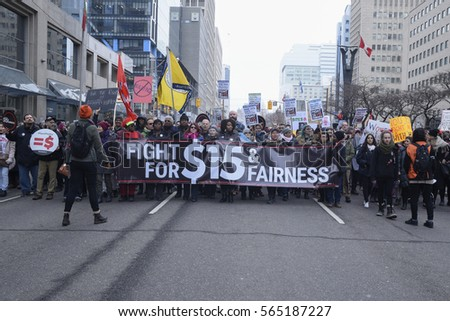 "TORONTO - JANUARY 21: A message to fight for $15 minimum wage being carried during the ""Women's March on Washington"" to protest against Trump presidency on January 21, 2017 in Toronto, Canada."